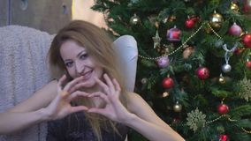 Chica joven bonita que hace un corazón con sus manos en fondo del árbol de navidad metrajes