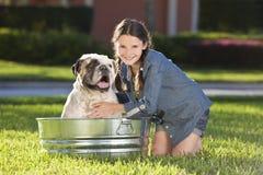 Chica joven bonita que lava su perro de animal doméstico en una tina Fotografía de archivo