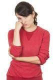 Chica joven bonita que lleva el top rojo que presenta con la mano Imágenes de archivo libres de regalías