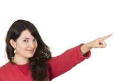 Chica joven bonita que lleva el top rojo que señala la mirada Imagen de archivo