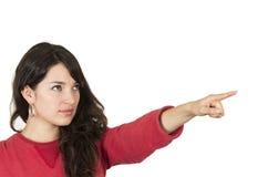Chica joven bonita que lleva el top rojo que señala la mirada Foto de archivo libre de regalías