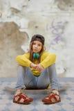 Chica joven bonita que presenta con un monopatín Foto de archivo libre de regalías