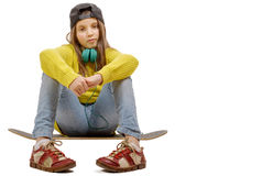 Chica joven bonita que presenta con un monopatín, asiento en patín Fotos de archivo libres de regalías