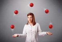 Chica joven que se coloca y que hace juegos malabares con las bolas rojas Imágenes de archivo libres de regalías