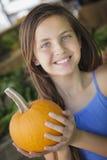 Chica joven bonita que se divierte con las calabazas en el mercado Fotografía de archivo libre de regalías