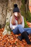 Chica joven bonita que se sienta al lado de un árbol en otoño Imagenes de archivo