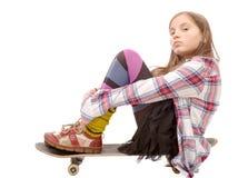 Chica joven bonita que se sienta en patín, en blanco Foto de archivo