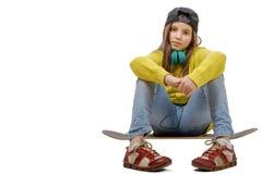 Chica joven bonita que se sienta en patín, en blanco Foto de archivo libre de regalías