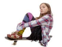 Chica joven bonita que se sienta en patín, en blanco Fotos de archivo