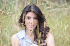 Chica joven bonita que se sienta en un campo Imágenes de archivo libres de regalías