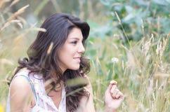 Chica joven bonita que se sienta en un campo Fotografía de archivo