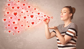 Chica joven bonita que sopla símbolos rojos del corazón Fotografía de archivo libre de regalías