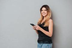 Chica joven bonita que sostiene el teléfono móvil y que mira la cámara Fotos de archivo