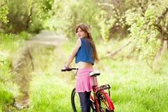 Chica joven bonita que sostiene la bici Fotografía de archivo
