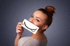 Chica joven bonita que sostiene la tarjeta blanca con el dibujo de la sonrisa Imagen de archivo