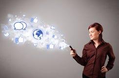 Chica joven bonita que sostiene un teléfono con los medios iconos sociales Imágenes de archivo libres de regalías