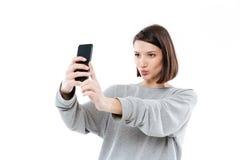 Chica joven bonita que toma el selfie en el teléfono móvil Fotografía de archivo