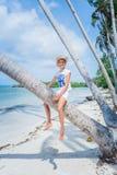 Chica joven bonita Sonrisa y el sentarse en la palmera en la playa tropical de la isla con agua clara Fotografía de archivo libre de regalías