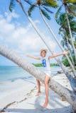 Chica joven bonita Sonrisa y el sentarse en la palmera en la playa tropical de la isla con agua clara Imágenes de archivo libres de regalías