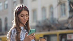 Chica joven bonita usando su situación de Smartphone con la taza de Cofee en la calle vieja y llevar sonriente en el azul rayado almacen de metraje de vídeo
