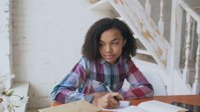 Chica joven cabelluda rizada adolescente de la raza mixta que se sienta en concentrar de la tabla enfocado aprendiendo las leccio almacen de video