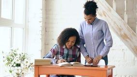 Chica joven cabelluda rizada adolescente de la raza mixta que se sienta en concentrar de la tabla enfocado aprendiendo lecciones  Imagenes de archivo