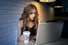Chica joven café-hermosa de Internet que comprueba las noticias en Internet y que bebe capuchino Una chica joven es consumición imágenes de archivo libres de regalías