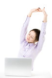 Chica joven cansada que estira delante del ordenador portátil Imagenes de archivo