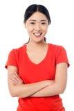 Chica joven casual que presenta, brazos cruzados Imágenes de archivo libres de regalías
