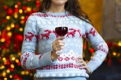 Chica joven cerca del árbol de navidad con la copa de vino Fotos de archivo