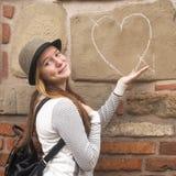 Chica joven cerca del corazón exhausto en la pared Amor Fotos de archivo