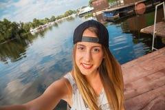 Chica joven cerca del río que toma Selfie Imagenes de archivo