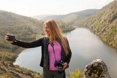 Chica joven cerca del río que toma Selfie Fotografía de archivo libre de regalías
