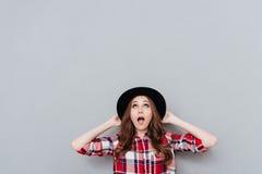 Chica joven chocada en el sombrero que mira para arriba el copyspace Imagenes de archivo