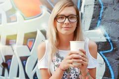 Chica joven con café a disposición, café de la calle Imagen de archivo libre de regalías