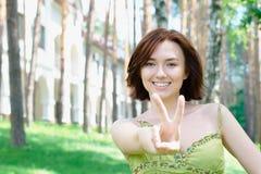Chica joven con dos dedos para arriba Imagen de archivo libre de regalías