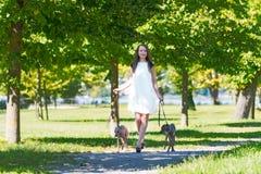 Chica joven con dos galgos en el parque Imagen de archivo