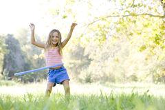 Chica joven con el aro del hula al aire libre que sonríe Foto de archivo