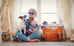 Chica joven con el bebé y perro listo para el viaje imagenes de archivo