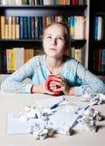 Chica joven con el bloque de los escritores que mira fijamente cuidadosamente Imagen de archivo