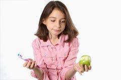 Chica joven con el cepillo de dientes y Apple Foto de archivo libre de regalías