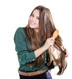 Chica joven con el cepillo para el pelo aislado Sonrisa Imágenes de archivo libres de regalías