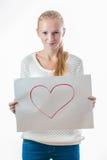Chica joven con el corazón en la hoja de papel Foto de archivo libre de regalías