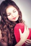 Chica joven con el corazón en manos Foto de archivo