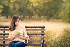 Chica joven con el cuaderno en un banco Imagenes de archivo
