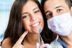 Chica joven con el dentista que señala en la boca Fotografía de archivo libre de regalías