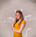 Chica joven con el dibujo de los cuernos y de las alas del diablo Imagenes de archivo