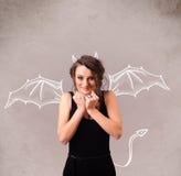 Chica joven con el dibujo de los cuernos y de las alas del diablo Foto de archivo