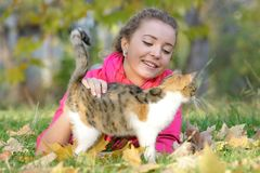 Chica joven con el gato al aire libre Fotos de archivo