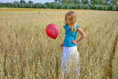 Chica joven con el globo rojo en trigo imagen de archivo